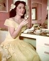 Актриса Элизабет Тейлор наслаждается чаем и пирожным в своей гримерной, около 1950 года.