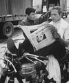 Image may contain: Paul Newman, Vehicle, Transportation, Motorcycle, Human, Person, Wheel, Machine, Text, and Newspaper